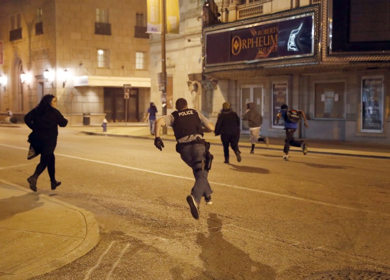 Image: Police chase people who were reportedly vandalizing property as demonstrators march.