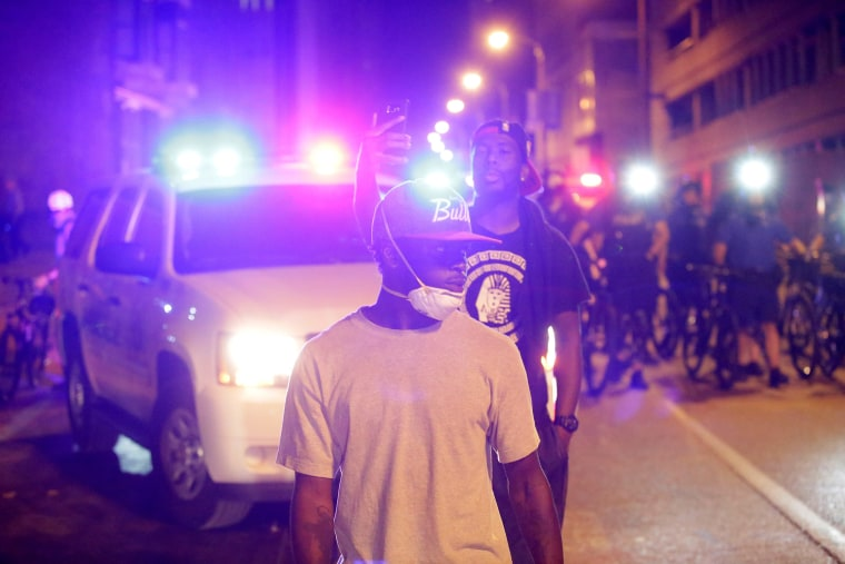 Image: Demonstrators are flooded by patrol car lights.
