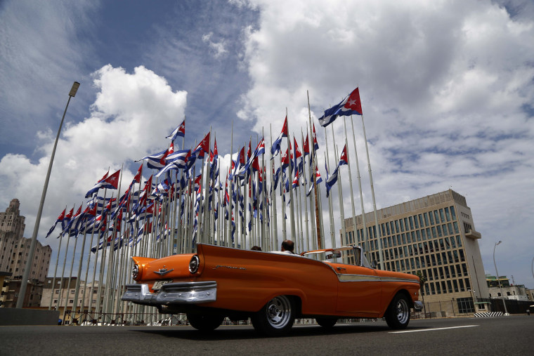 Image: Tourists ride a classic American convertible car along the Malecon beside the United States embassy as Cuban flags fly