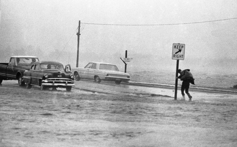 A man clings to road sign in New Bern, North Carolina, during a gust of high wind as Hurricane Ginger approached on Sept. 30, 1971.