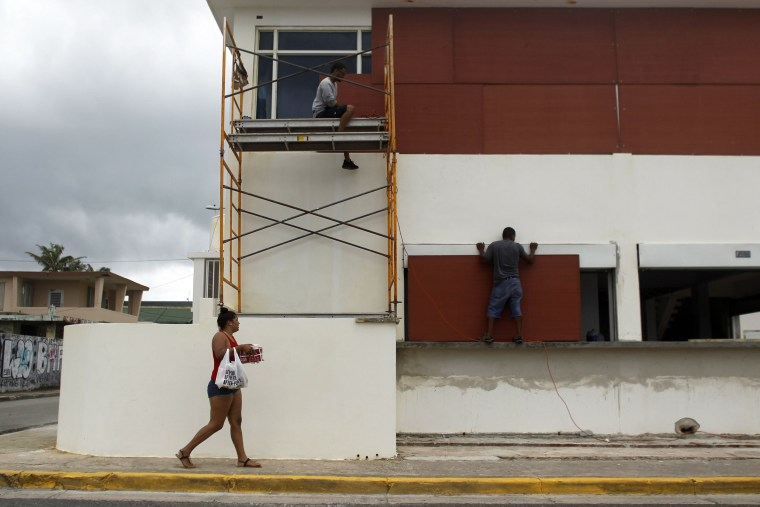 Image: People board up windows of a business in preparation for Hurricane Maria
