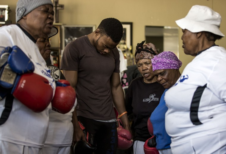 "Image: Gladys Ngwenya, 77, center, and Constance Ngubane, 79, second right, pray with others ahead of taking part in a ""Boxing Gogos"" (Grannies) training session"
