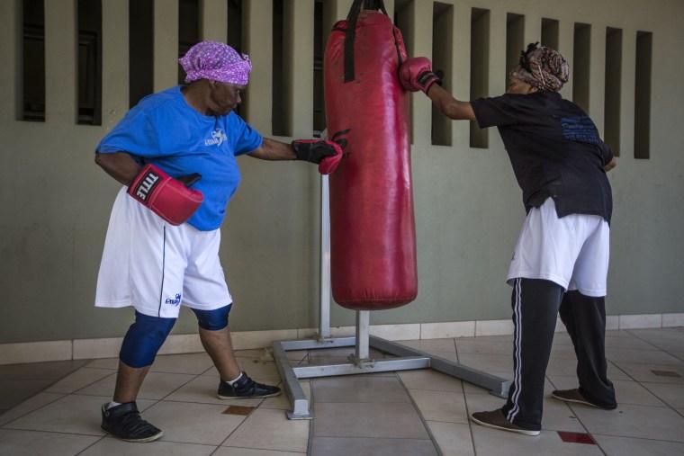 Image: Gladys Ngwenya, 77, right, and Constance Ngubane, 77, use a punch bag