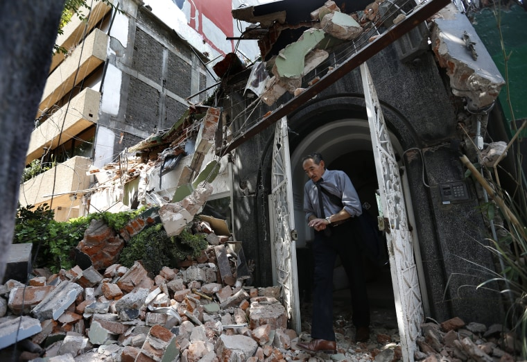 Image: A man walks out of the door frame of a building that collapsed