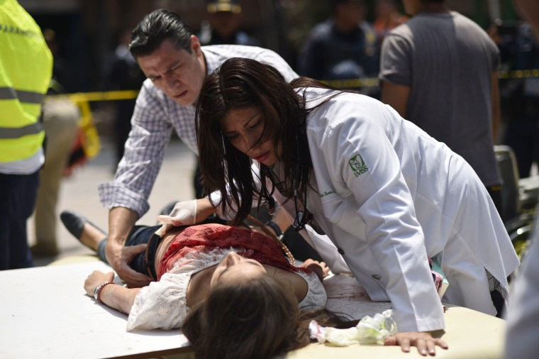 Image: An injured woman is treated after a powerful earthquake in Mexico City