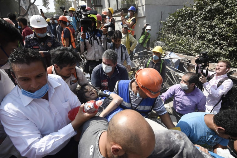 Image: A woman is carried away after being pulled out of the rubble in Mexico City