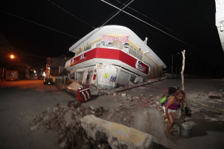 Image: A woman walks past a collapsed building in Jojutla, Morelos state