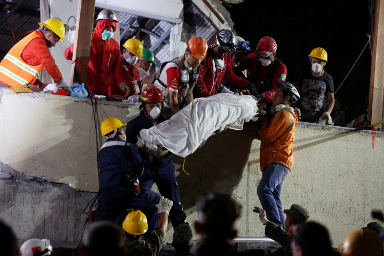 Image: Rescue workers remove a dead body after searching through rubble in Mexico City
