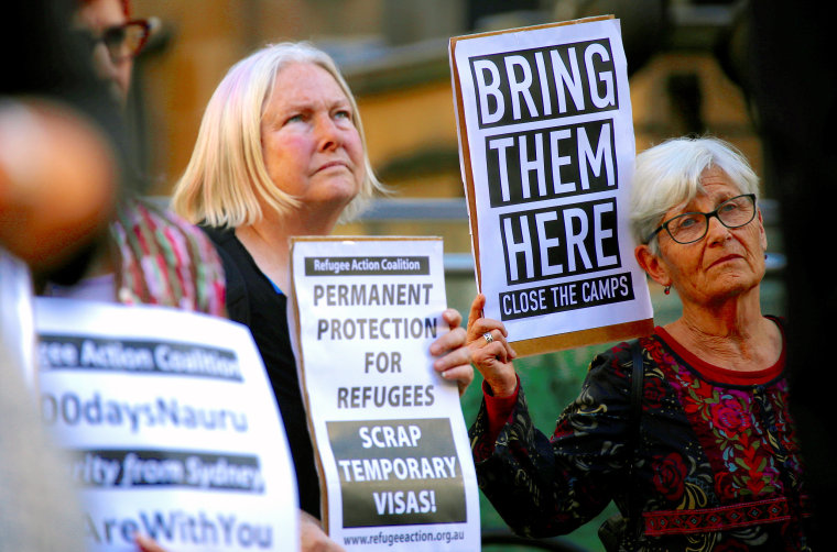 Refugee advocates hold placards and banners during a protest in central Sydney