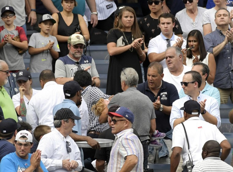 Image: Baseball fans reacts as a young girl is carried out after being hit by a line drive