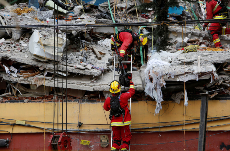Image: Rescue team members work on the rubble of a collapsed building after an earthquake hit Mexico City