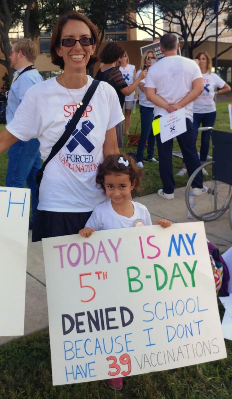 Image: Dene Shulze-Alva and her daughter Sage, 5, protest against vaccine laws in Houston