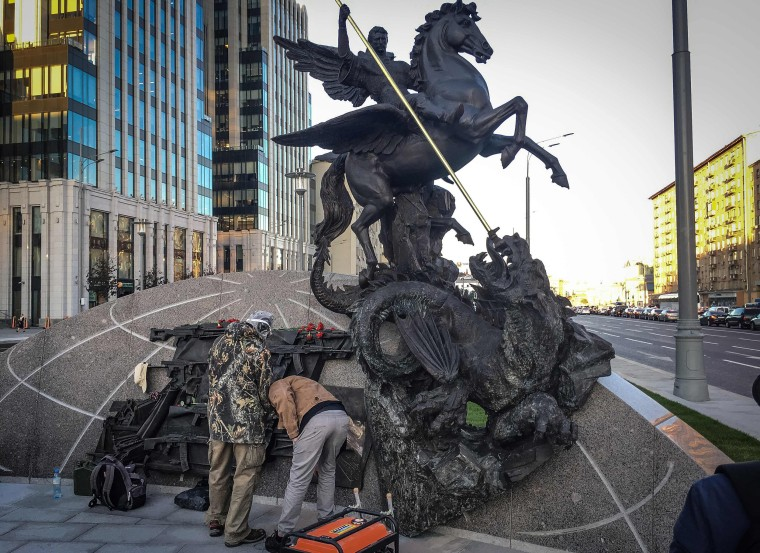 Image: Men remove a sketch allegedly featuring German StG44 rifle from a fragment of the newly unveiled monument