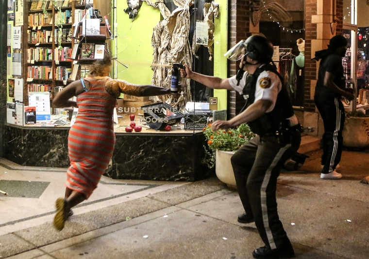 Image: A protester is sprayed with mace by riot police after throwing a chair through a window of a business during the second night of demonstrations after a not guilty verdict in the murder trial of former St. Louis police officer Jason Stockley in St.