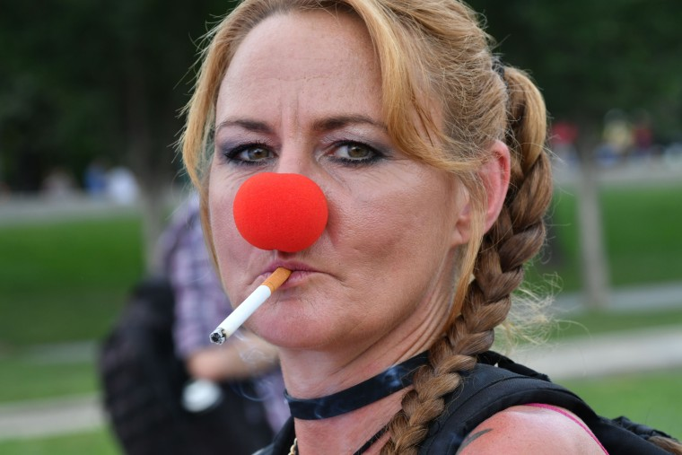 Image: A woman wearing a clown's nose smokes a cigarette