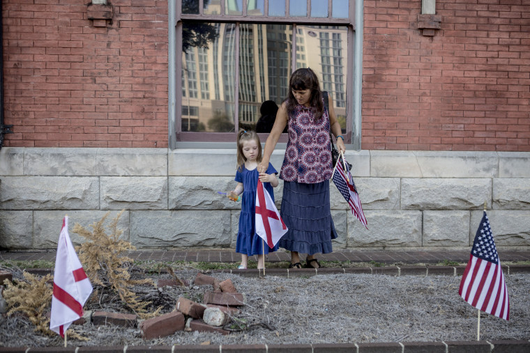 Image: Leigh Ford and her daughter Lydia, 5, plant American and state of Alabama flags outside of Train Depot.