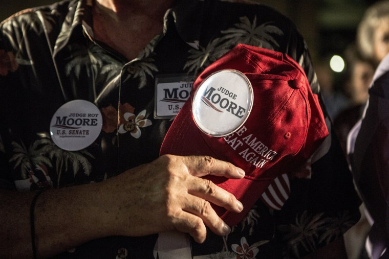 Image: Joe Green holds his Make America Great Again hat over his heart while pledging allegiance at Moore's debate watching party.