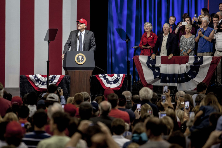 Image: Strange puts on a Make America Great Again hat at in front of supporters at his rally.