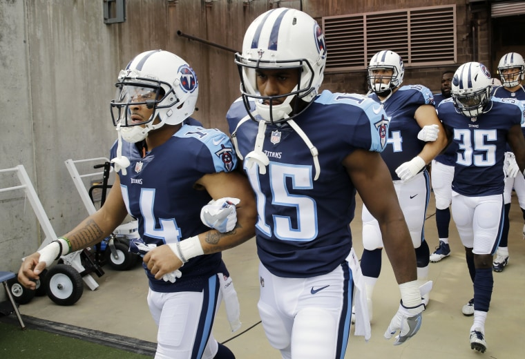 Image: Tennessee Titans wide receiver Eric Weems (14) and wide receiver Darius Jennings (15) walk to the field with arms linked after the national anthem