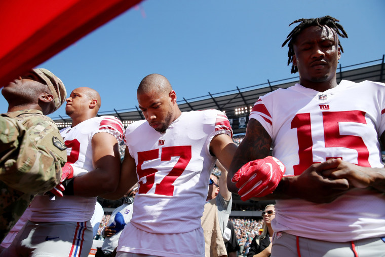 Image: Keenan Robinson #57 and  Brandon Marshall #15 of the New York Giants link arms during the national anthem