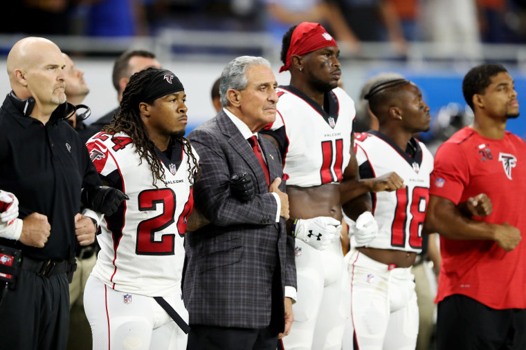 Image: Atlanta Falcons owner Arthur Blank joins arms with his players during the playing of the national anthem