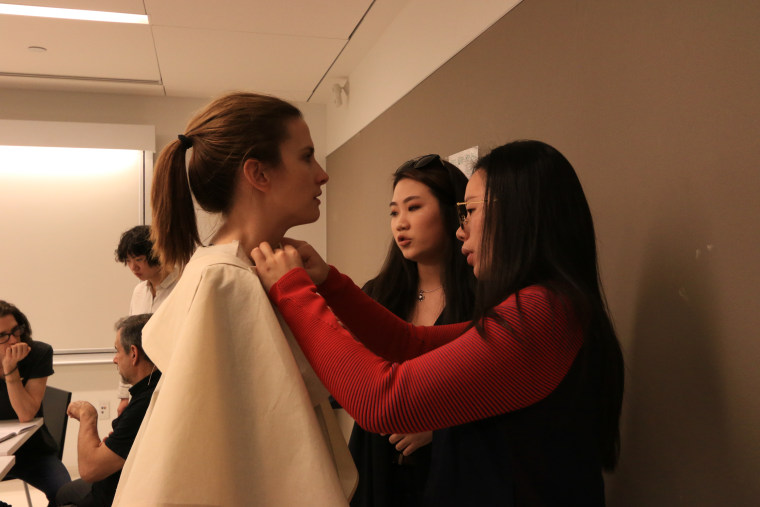 Parsons students Claudia Poh (center) and Estee Bruno (right) work on the patten for a coat for Christina Mallon.