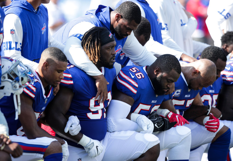 Image: Buffalo Bills players kneel during the American National anthem