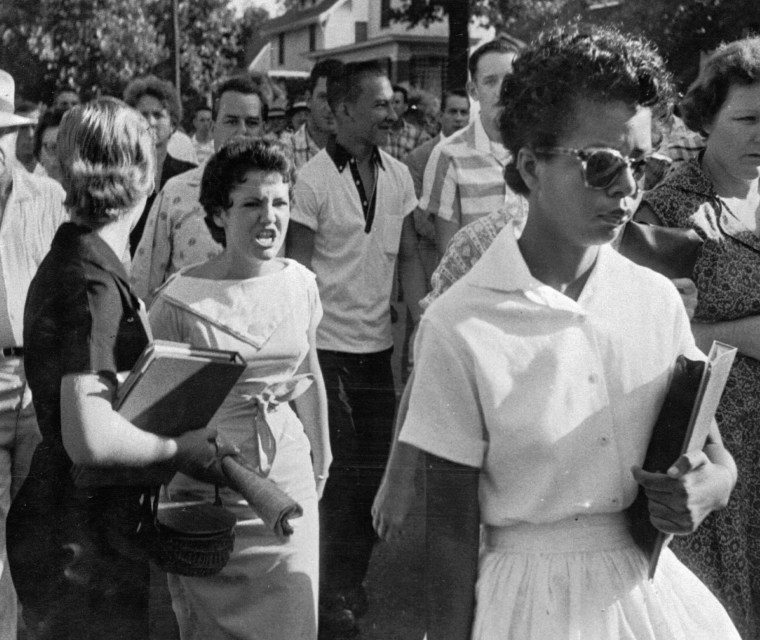 Students of Central High School in Little Rock, Ark., including Hazel Bryan, shout insults at Elizabeth Eckford as she calmly walks toward a line of National Guardsmen.
