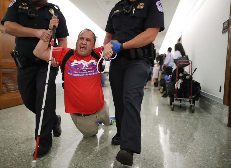 Image: U.S. Capitol Police drag a blind protester out of a Senate Finance Committee hearing