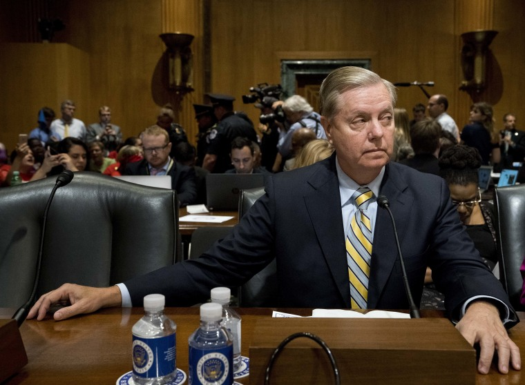 Image: Sen. Lindsey Graham, R-S.C. waits as people in wheelchairs are removed