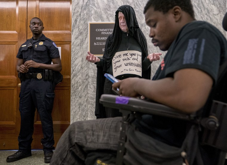 "Image: David Barrows of Washington, center, dresses as the grim reaper and wears a sign that reads ""Give me your poor, your sick, and your uninsured\"""