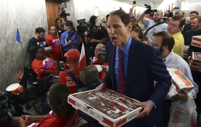Image: Sen. Ron Wyden, D-Ore., carries pizza as he talks with people in wheelchairs