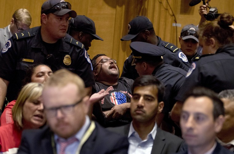 Image: A man in a wheelchair is removed after disrupting a Senate Finance Committee hearing to consider the Graham-Cassidy health care proposal