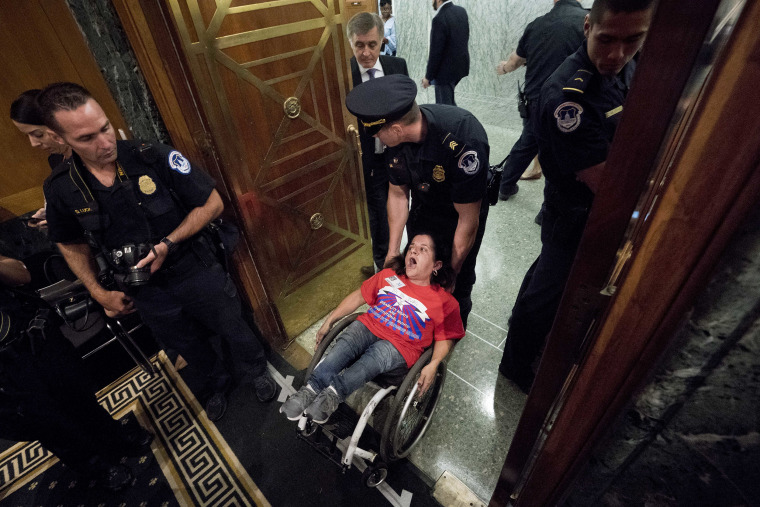 Image: A woman in a wheelchair is removed after disrupting a Senate Finance Committee hearing to consider the Graham-Cassidy health care proposal