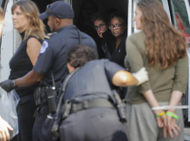 Image: U.S. Capitol Police detain and process people who came to the Senate Finance Committee hearing