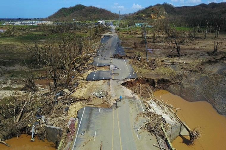 Image: A man rides his bicycle through a damaged road in Toa Alta, Puerto Rico