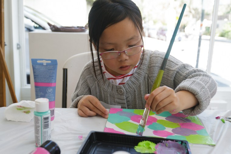 Ten-year-old Suri paints at a Kids & Art Foundation workshop. The group organizes arts events for pediatric cancer patients, survivors, and their siblings.
