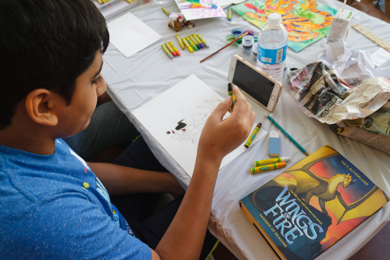 Eleven-year-old Raaif draws a dragon at a Kids & Art Foundation event.