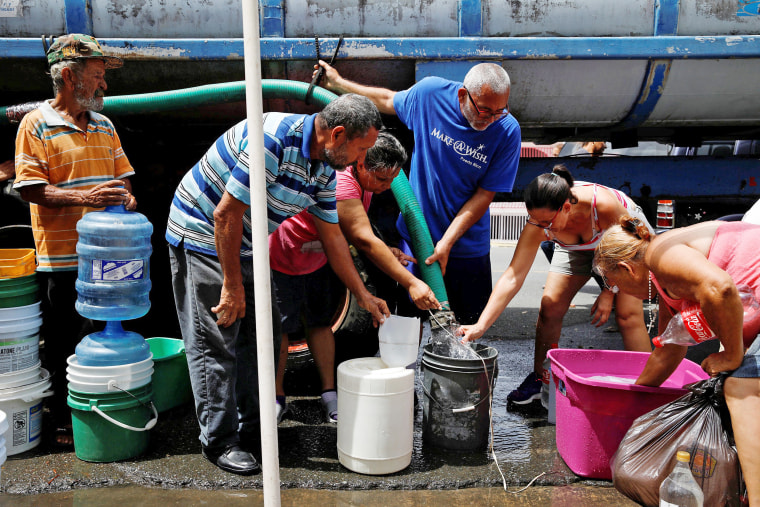 Image: People queue to fill containers with water from a tank truck at an area hit by Hurricane Maria in Canovanas