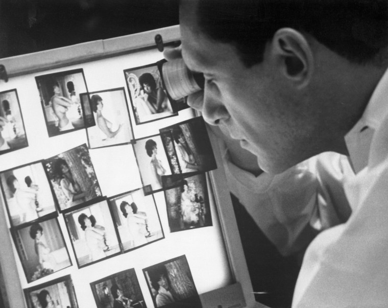 Image: Playboy Publisher Hugh Hefner Observing Photographs