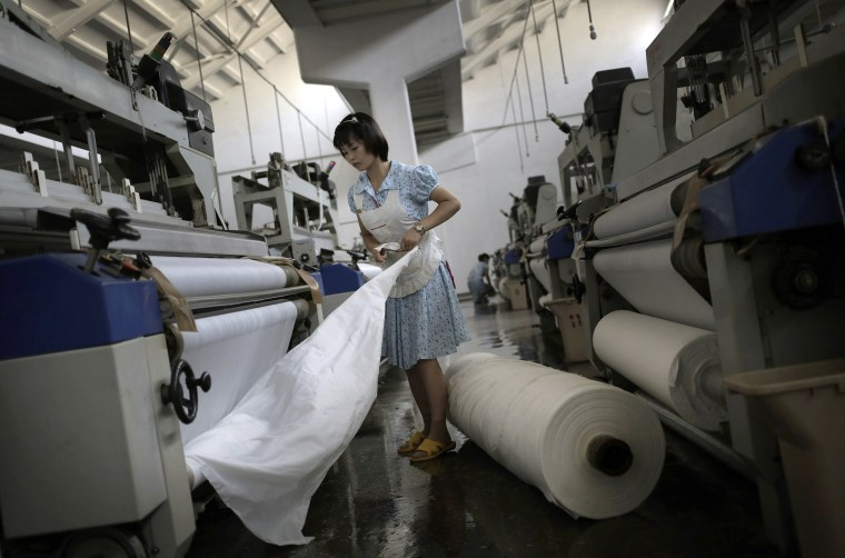 Image: A worker stretches out a bale of cloth at the Kim Jong Suk Pyongyang textile factory