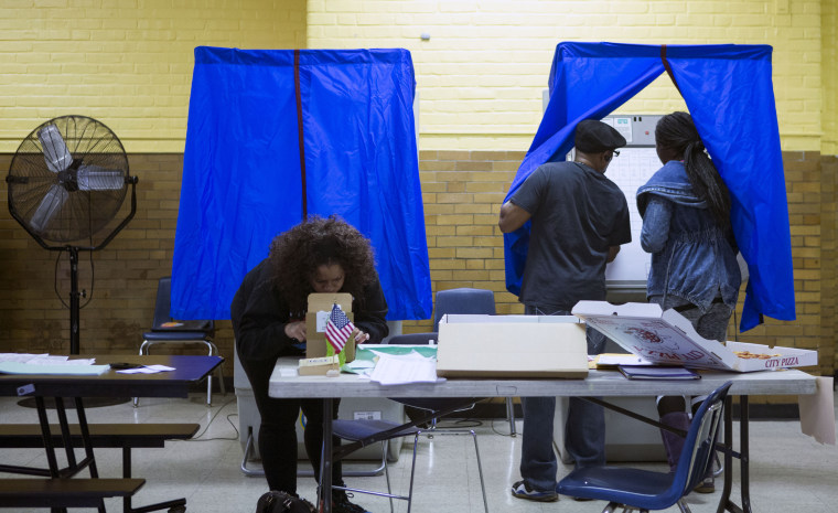 Image: A woman enters a voting booth to cast her vote at Vare Edwin Middle School in Philadelphia