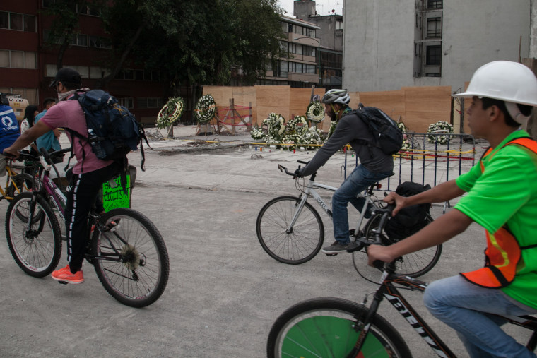 A cyclist brigade passes in front of a razed building where numerous people died following Mexico's devastating earthquake.