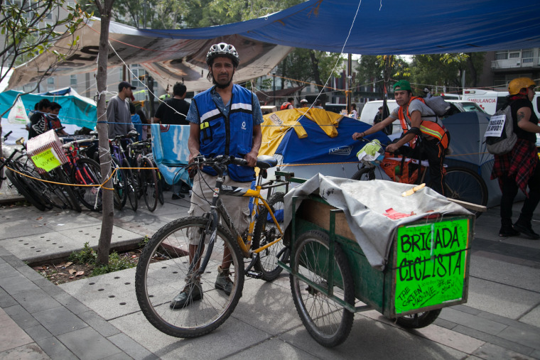 Rafael Mendoza delivers essential supplies with his bike cart twelve hours a day.