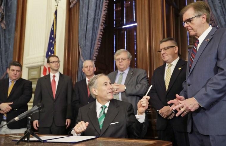 Image: Gov. Greg Abbott, center, offers a pen to Lt. Gov. Dan Patrick, right, after he signed SB7