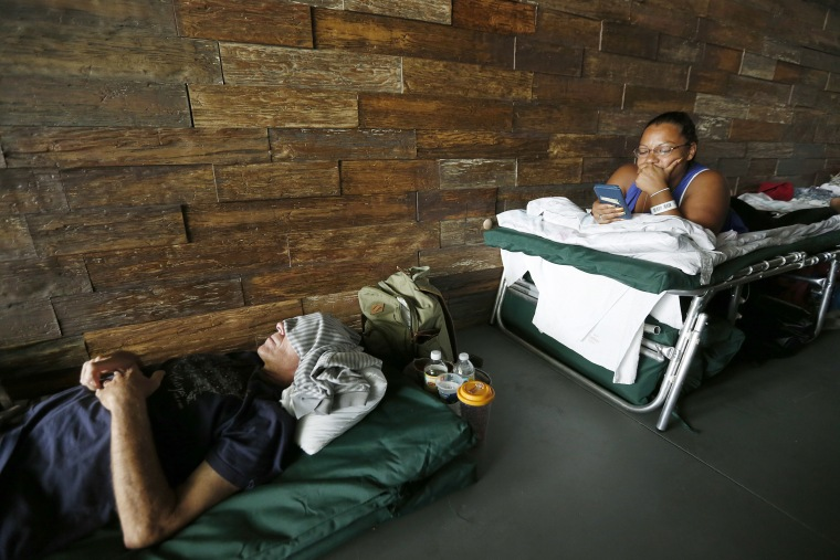 Image: Margarita Lopez, right, as she looks at her phone and RS Steidle naps at a special needs shelter at Florida International University in Miami