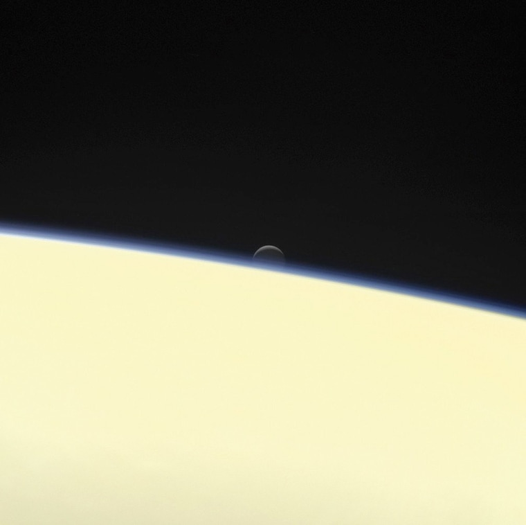 Image: The moon Enceladus and the edge of Saturn as seen from the Cassini spacecraft on its descent towards the planet.