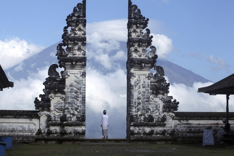 Image: A Balinese man watches the Mount Agung volcano almost covered with clouds as he stands at a temple in Karangasem, Bali