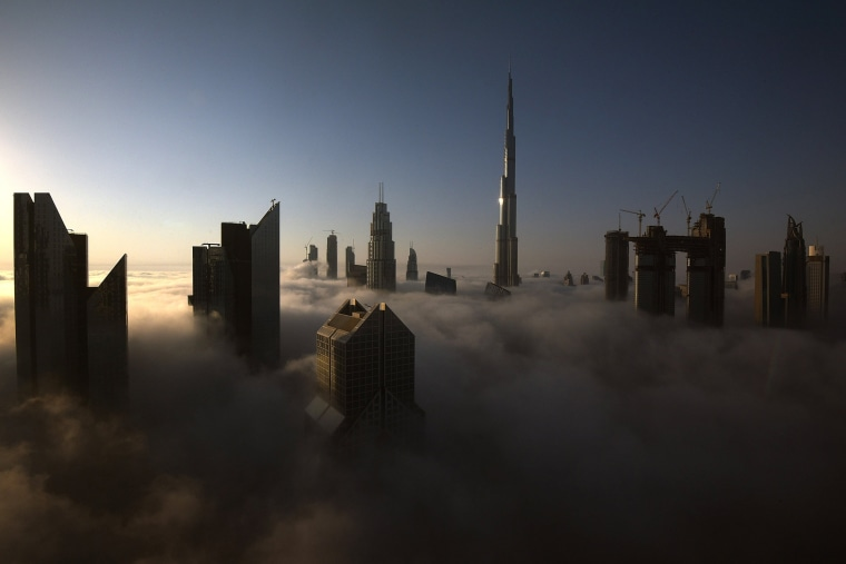 Image: Skyscrapers pierce clouds during a heavy fog in Dubai