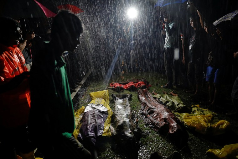 Image: People gather under heavy rain around bodies of Rohingya refugees after their boat with passengers fleeing from Myanmar capsized off the Inani beach near Cox's Bazar